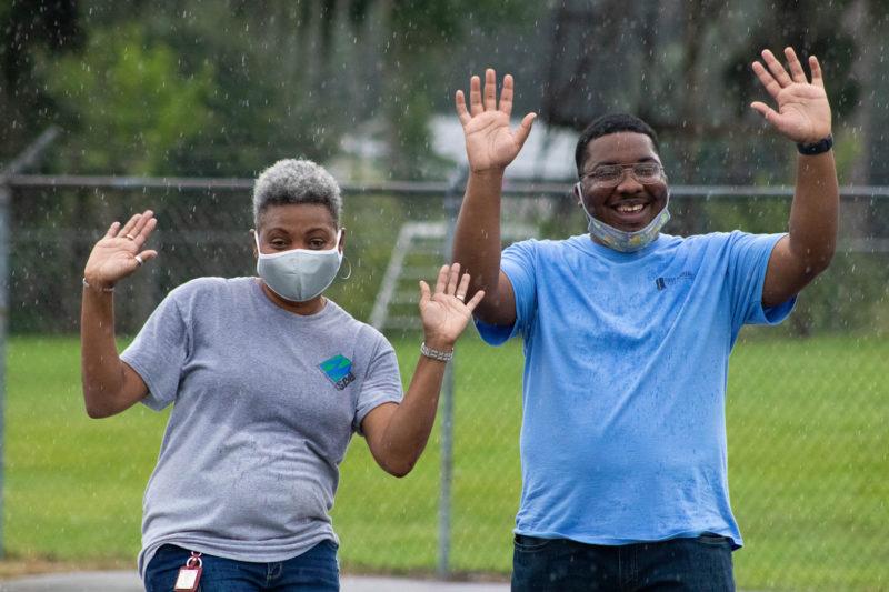 two volunteers smiling in the rain