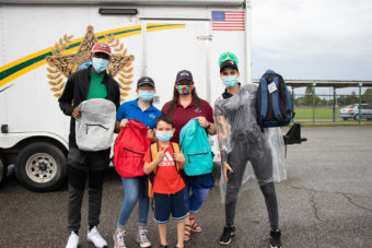 volunteers with young girl holding backpacks