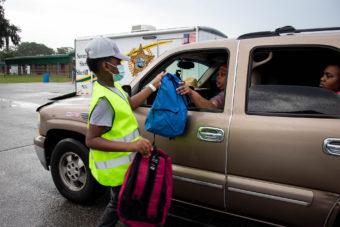 volunteer handing backpack to people in car