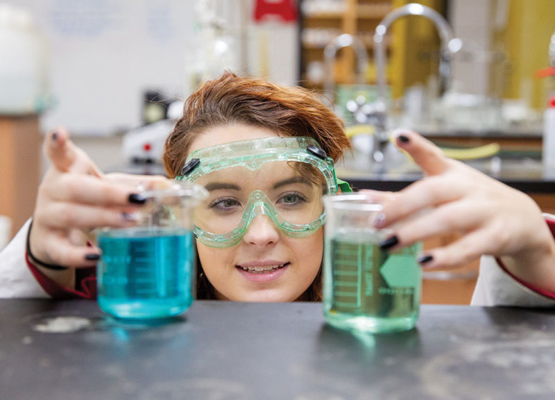 Young girl wearing goggles looking at two filled beakers.