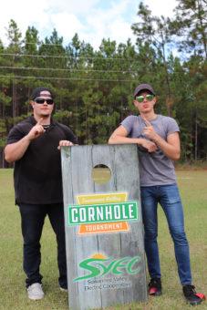 two men posing near cornhole tournament board