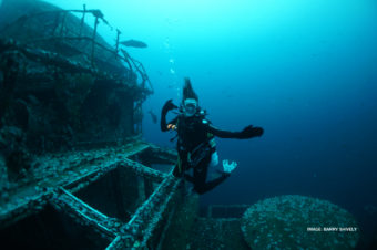 diver exploring ship at bottom of ocean